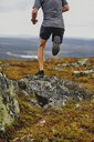 Man trail running on rocky cliff top, Keimiotunturi, Lapland, Finland - CUF20110