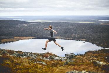 Man sprinting on rocky cliff top, Keimiotunturi, Lapland, Finland - CUF20116