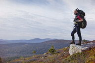 Hiker enjoying view on rock, Keimiotunturi, Lapland, Finland - CUF20137