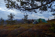 Hikers relaxing in front of tent, Keimiotunturi, Lapland, Finland - CUF20140