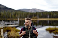 Hiker with lake in background, Kesankijarvi, Lapland, Finland - CUF20143