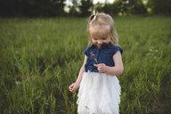 Girl in field holding flower - CUF20146