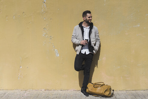 Smiling bearded man with coffee to go, leaning on wall - AFVF00589