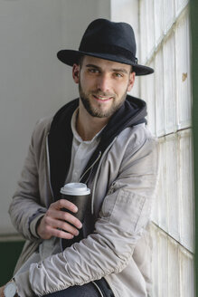 Smiling bearded man wearing black hat, holding coffee to go - AFVF00592