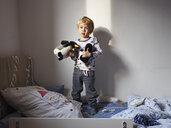 Portrait of little boy standing on bed with his soft toys - MUF01531