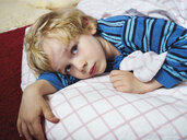 Portrait of little boy lying on the floor with bedding - MUF01537