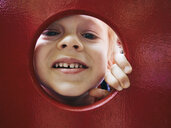 Portrait of smiling little boy looking through hole on playground - MUF01540