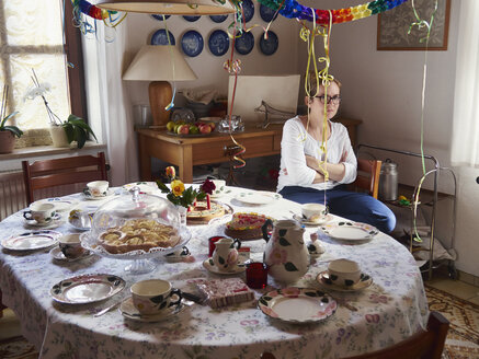 Woman in bad mood waiting at laid  table for guests - MUF01552