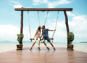 Thailand, Koh Lanta, kissing couple sitting on swings in front of the sea - GEMF02049