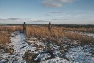 Sweden, Sodermanland, two men standing in remote landscape in winter - GUSF00913