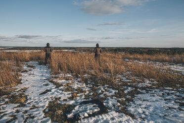 Sweden, Sodermanland, two men standing in remote landscape in winter - GUSF00913