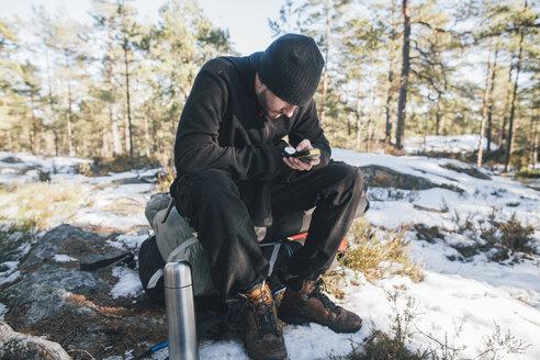 Sweden, Sodermanland, backpacker resting in remote landscape in winter using GPS tracker - GUSF00928