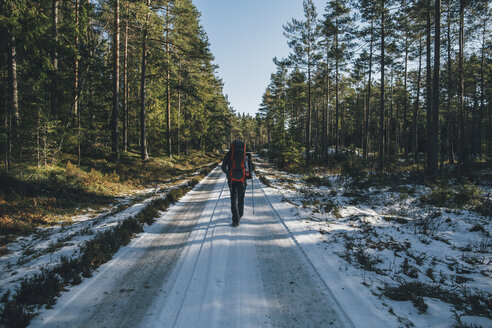 Sweden, Sodermanland, backpacker hiking on path in remote forest in winter - GUSF00931