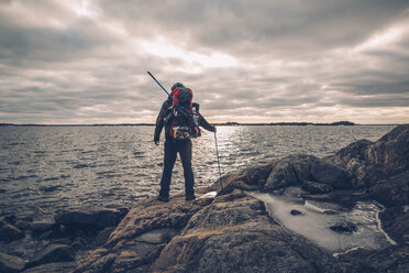 Sweden, Sodermanland, backpacker standing at the seashore under cloudy sky - GUSF00937
