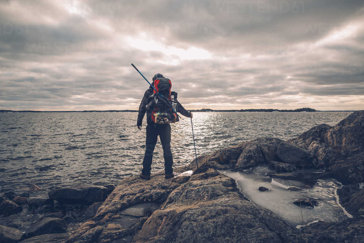 Sweden, Sodermanland, backpacker standing at the seashore under cloudy sky - GUSF00937 - Gustafsson/Westend61