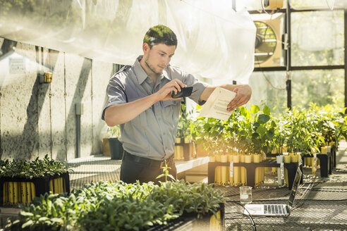 Scientist photographing paperwork in plant growth research facility greenhouse - CUF20249