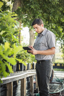 Scientist updating digital tablet at plant growth research facility - CUF20255