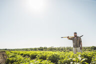 Bearded man in vegetable patch carrying hoe on shoulder looking at camera - CUF20288