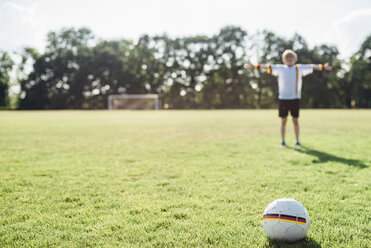 Boy with outstretched arms standing on soccer field between German soccer ball and goal - MJF02307