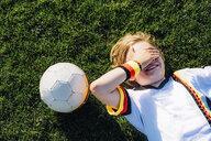 Boy in German soccer shirt lying on grass, covering eyes - MJF02310