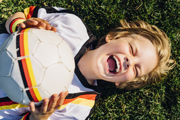 Boy in German soccer shirt lying on grass, laughing happily - MJF02313