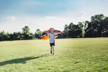 Boy, enthusiastic for soccer world championship, waving German flag - MJF02322