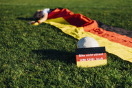 Boy sleeping under German flag with do not disturb sign due to soccer world championship - MJF02328