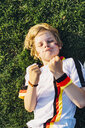Boy in German soccer shirt lying on grass, keeping fingers crossed for world chamiponship - MJF02340