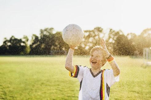 Boy wearing German soccer shirt screaming for joy, standing in water splashes - MJF02346