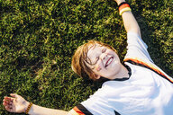 Boy in German soccer shirt lying on grass, laughimg - MJF02349
