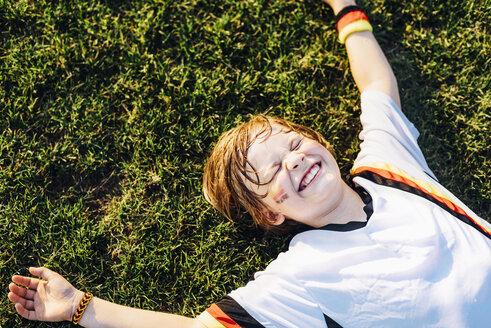 Boy in German soccer shirt lying on grass, laughimg - MJF02349