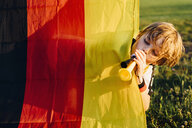 Boy standing behind German flag, blowing horns for soccer world championship - MJF02352