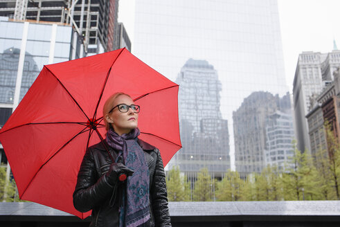 Female tourist with red umbrella looking up from One World Trade Center, New York, USA - CUF20449