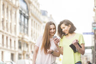Two young women strolling on street reading smartphone texts, Paris, France - CUF20479