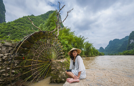 Woman with traditional straw hat resting at water wheel at the Yulong river in Guangxi, China - CUF20518