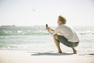 Mature man crouching on beach taking photograph of sea, using smartphone - CUF20521
