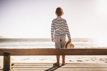 Young boy standing on wooden decking at beach, looking at sea, rear view - CUF20527