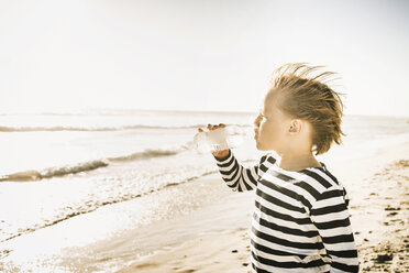 Young boy on beach, drinking from water bottle - CUF20536