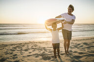 Father and son standing on beach, holding surfboard - CUF20542
