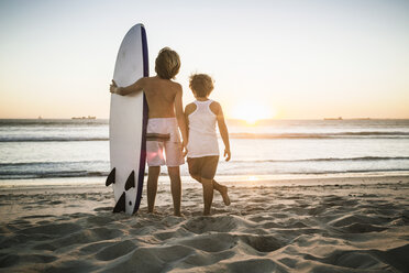 Two young boys standing on beach,with surfboard, looking at ocean, rear view - CUF20545