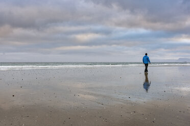 Man walking along beach, rear view, Westfjords, Iceland - CUF20680