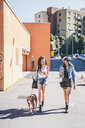 Two young women walking pit bull in urban housing estate - CUF20839