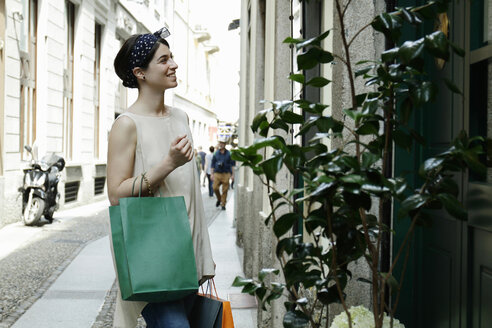 Woman with shopping bags reading menu outside restaurant, Milan, Italy - CUF20848