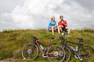 Cyclists relaxing and chatting on grassy hilltop - CUF20881