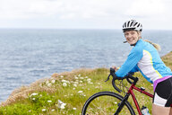 Cyclist stopping on hill overlooking ocean - CUF20884