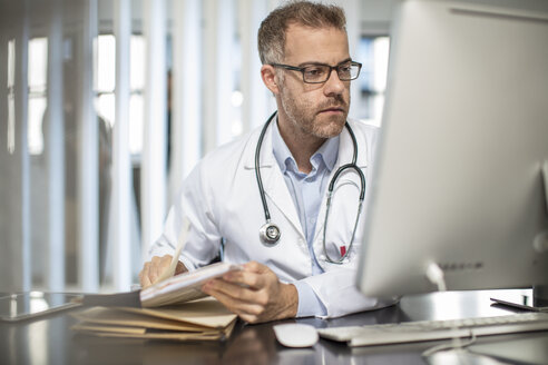 Doctor working at desk in medical practice - ZEF15502