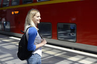 Portrait of blond woman with backpack on platform - BFRF01827