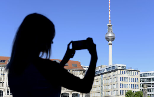 Silhouette of young woman photographing Berlin TV Tower - BFRF01839