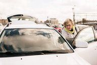Senior woman standing by car in parking lot against sky - MASF07624