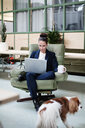 Businesswoman using laptop and having coffee while sitting on chair by dog at office - MASF07657